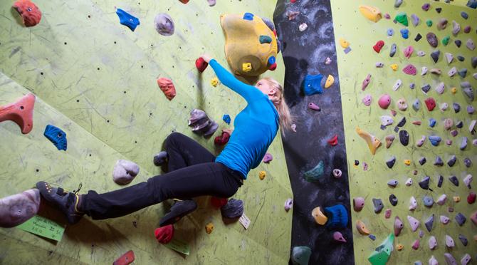 Nainen harrastamassa seinäkiipeilyä.
